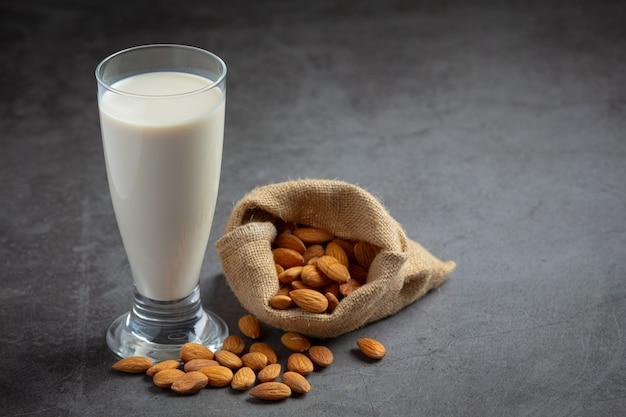 Almond milk with almond on dark background