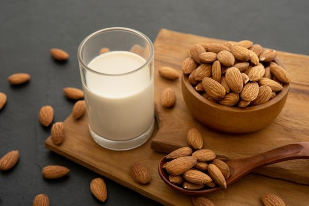 Миндальное молоко с миндалем в деревянной ложке и миске на деревянном