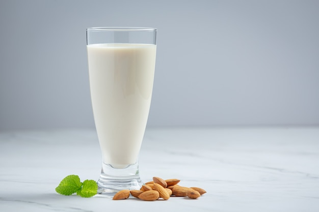 Almond milk with almond on marble background