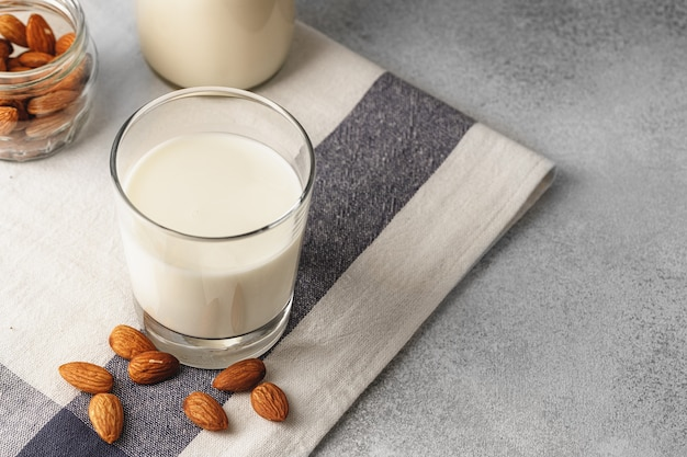 Almond milk with almond nuts surrounding the glass