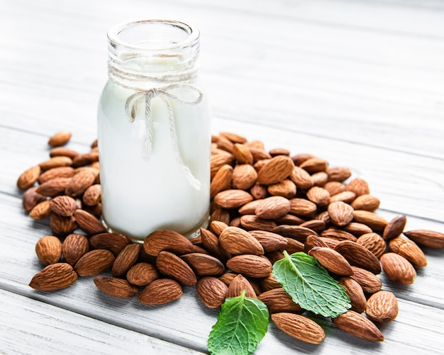 Almond milk with almonds on a wooden table