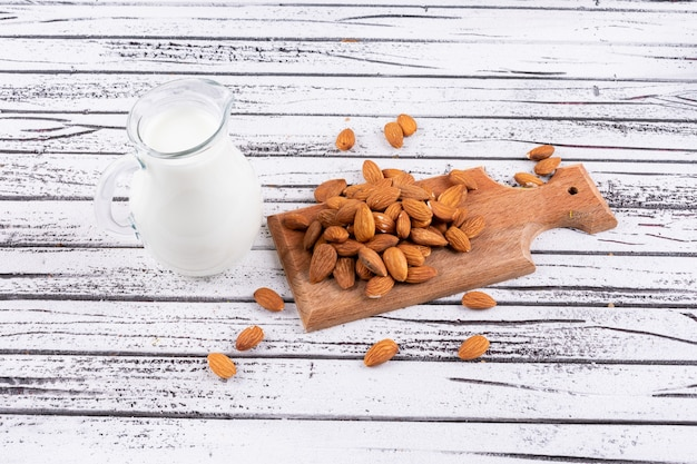 Almond and milk on a wooden cutting board on a white wooden table