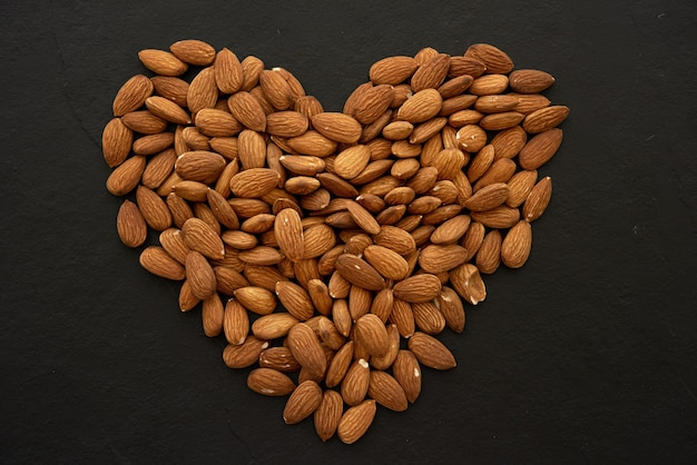 Almond nuts forming a heart-shape on black background.