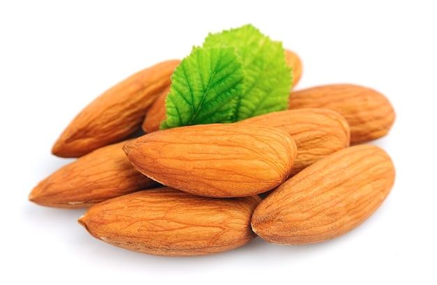 Группа миндальных орехов с листом на белом