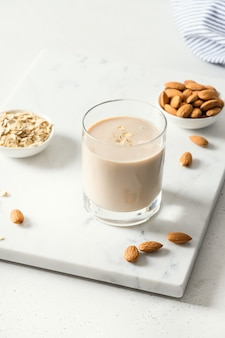 Almond and oatmeal milk on white background