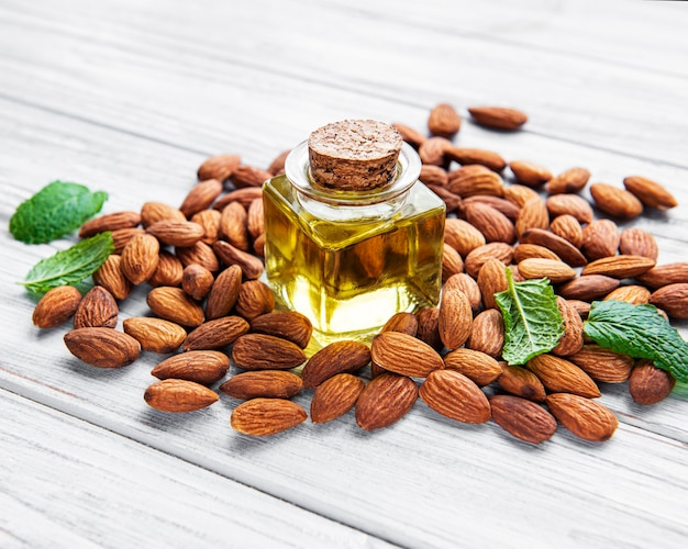 Almond oil and  almonds on white wooden background. top view