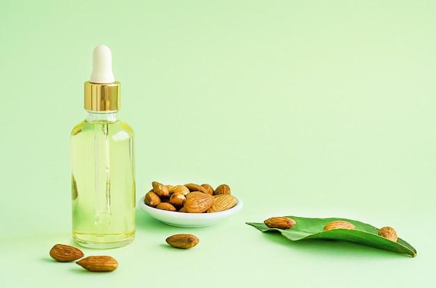 Миндальное масло и целый орех для ухода, массажа и приготовления пищи на зеленом фоне. копировать пространство