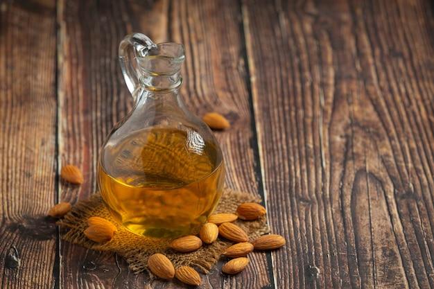 Almond oil in bottle on dark wood background