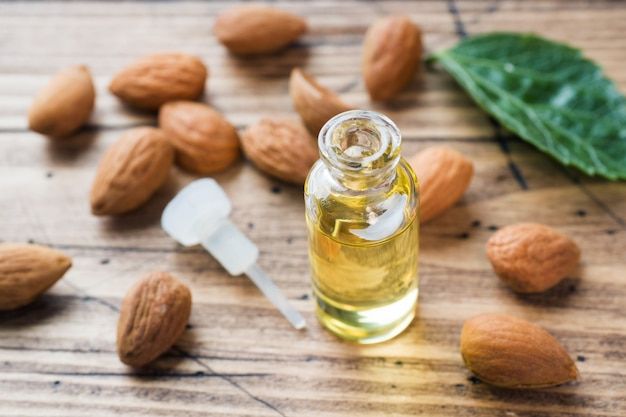 Almond oil in bottle on wooden table. concept spa, aromatherapy and medicine.