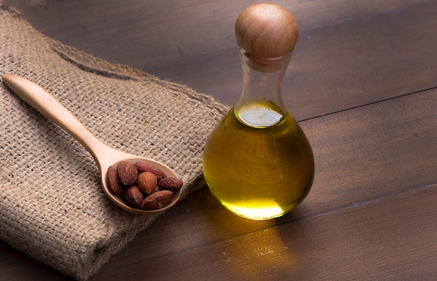 Almond oil in bottles place side by side with an almond seed on a sack bag with a wooden background
