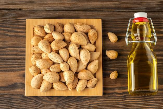 Миндальное масло с бутылкой и ореховой скорлупой миндаль по дереву