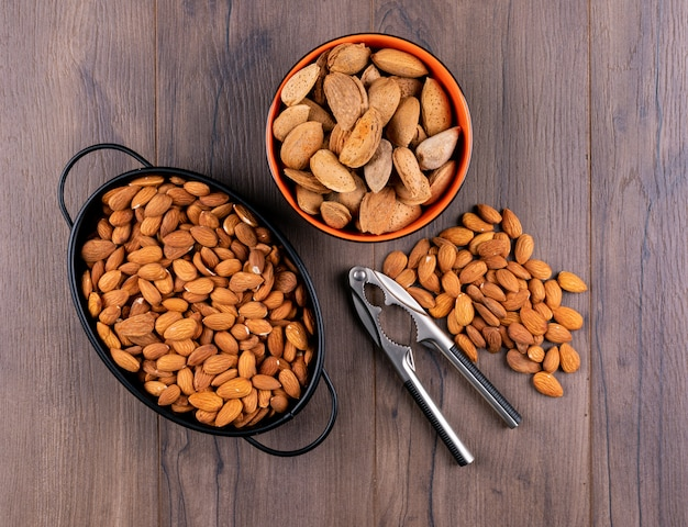 Almond in a pan with scattered almonds high angle view on a wooden table