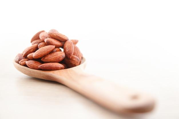 Гранулы миндаля в деревянной ложке. положите на деревянный пол. концепция продовольственной фотографии.