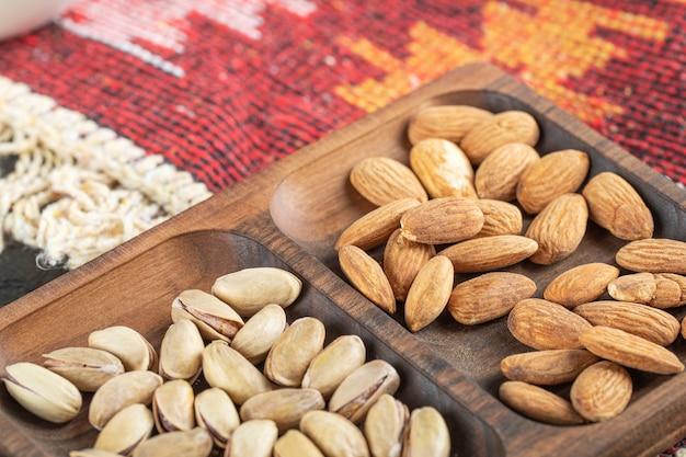 Mandorle e pistacchi in un piatto di legno