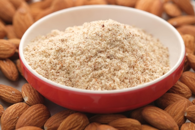Almond powder in a container with almond nut on table