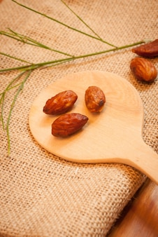 Almond on sack with wooden spoon.