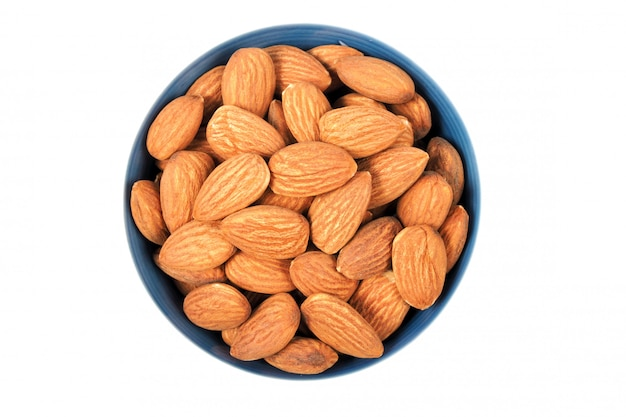 Almond seeds in bowl isolated on white background.  top view
