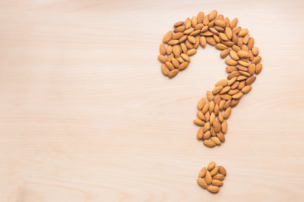 Almond in the shape of question mark on light wooden background. nuts on the table