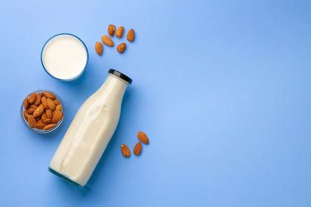 Almond vegan milk in bottle with dry nuts on blue