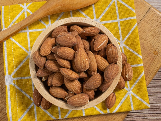 The almond in wood bowl on wood table for food and health  concept