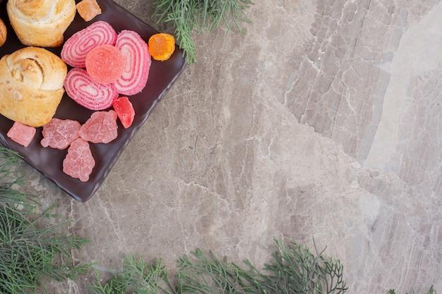Миндальные обертывания и мармелад рядом с сосновыми листьями на мраморе.