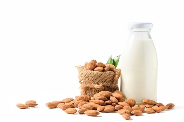 Миндаль и миндальное молоко на белом фоне