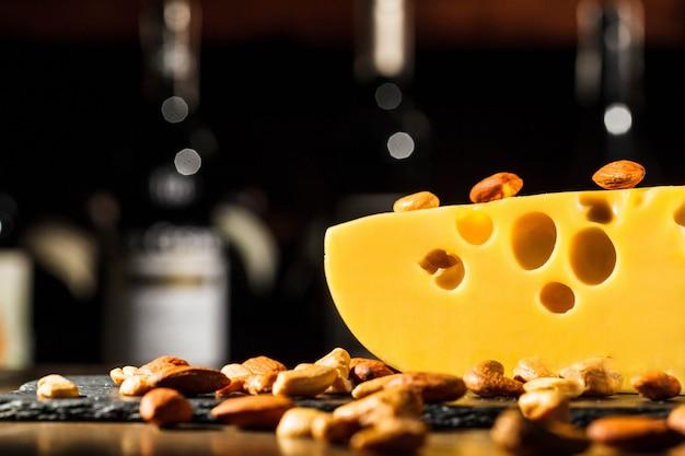 Миндаль и арахис лежат на куске швейцарского сыра