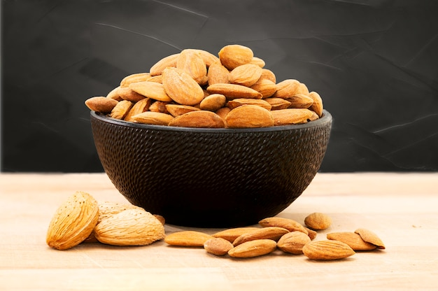 Almonds in black porcelain bowl on wooden table with unfocused