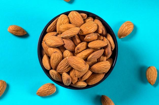 Almonds bowl on blue