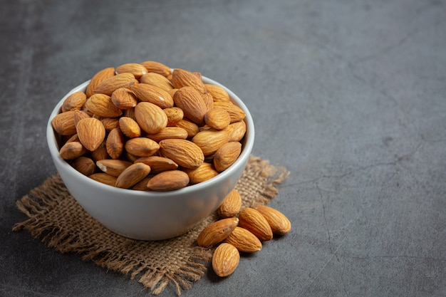 Almonds in bowl on dark background
