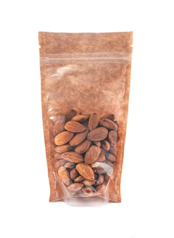 Almonds in a brown paper bag. doy-pack with a plastic window for bulk products. close-up. white background. isolated.