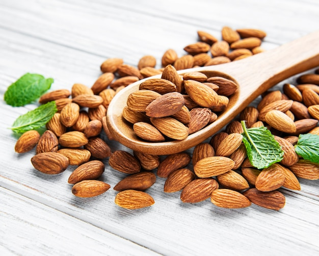 Almonds in brown spoon on wooden background