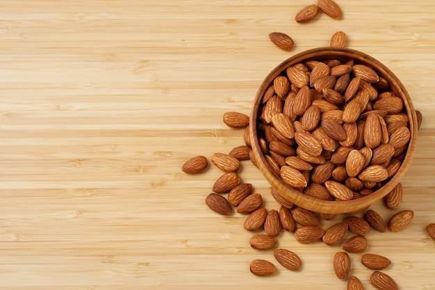 Almonds in brown wooden bowl on old wooden table