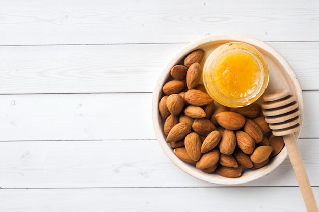 Almonds and a can of honey on the table background