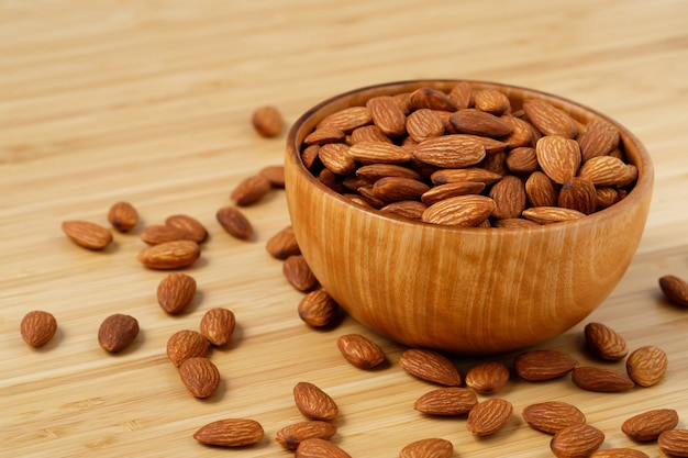 Almonds on dark stone table with wood spoon or scoop. almond in wooden bowl. nuts freely laid on dark board.