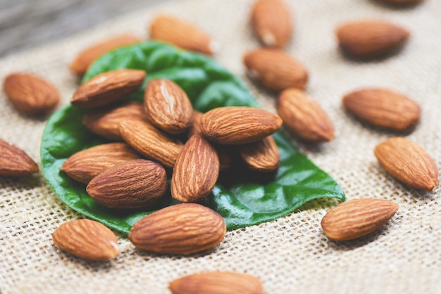 Almonds on green leaf / close up almond nuts natural protein food and for snack on sack