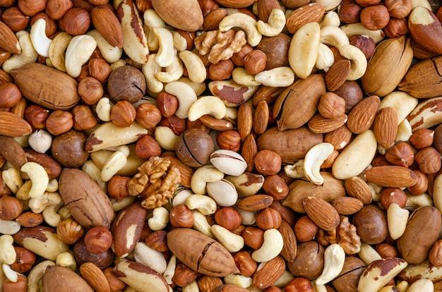 Смешанные вместе миндаль, фундук, кешью, бразильские орехи, грецкий орех, макадамия, пекан и фисташки. естественный фон. здоровая пища. вид сверху.