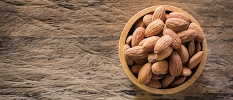 Almonds in brown bowl on textured wooden background.