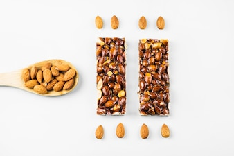 Almonds in wooden spoon with proteins bar on white background