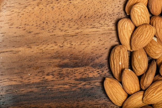 Almonds isolated on wooden background. top view. macro photography