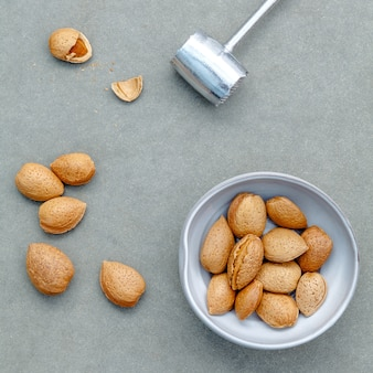 Almonds kernels and whole almonds on concrete background.