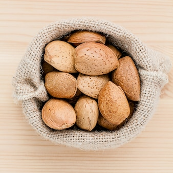 Almonds kernels and whole almonds on wooden background.