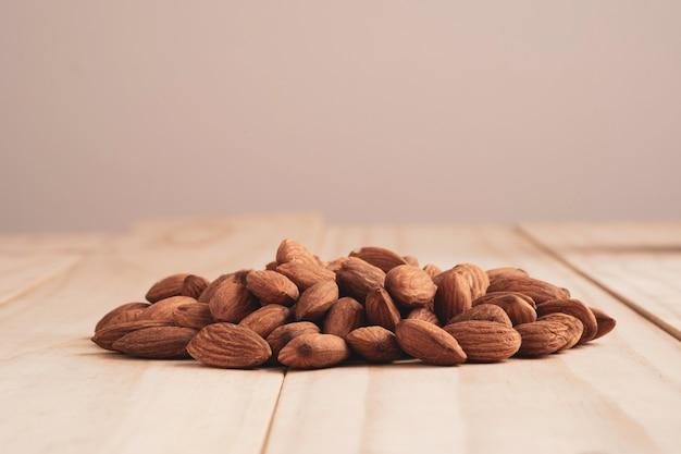 コピースペースのある木製のテーブルにアーモンドナッツの山。アーモンドナッツは、高タンパク、低脂肪、必須アミノ酸を含む健康的なダイエット食品です。