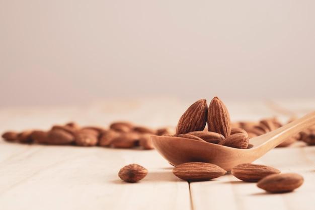 木のスプーンにアーモンドナッツを入れ、コピースペースのあるテーブルに注ぎます。アーモンドナッツは、高タンパク、低脂肪、必須アミノ酸を含む健康的なダイエット食品です。
