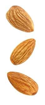Almonds nut kernel three whole soaring, falling, flying isolated