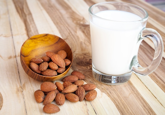 Almonds nuts and almond milk on wooden table background
