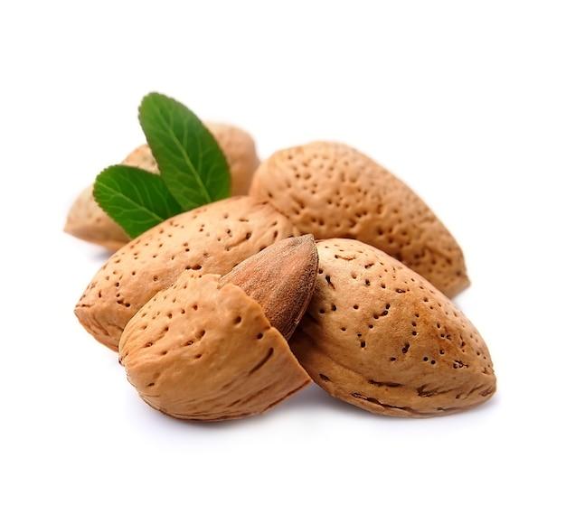 Крупный план орехов миндаля на белизне с крупным планом листьев.