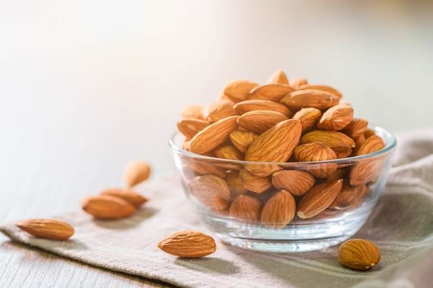 Almonds nuts   peeled in glass bowl on wood table with sun light on morning.