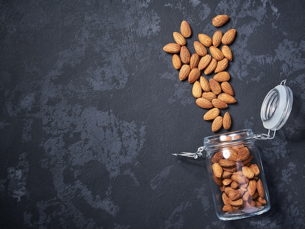 Almonds in an open glass jar on black table, with copy space ,top view