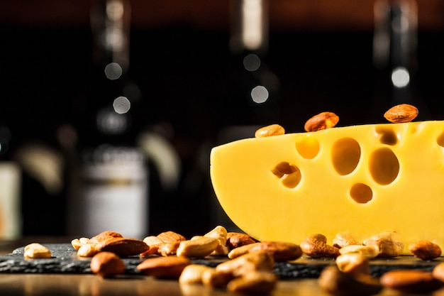 Almonds and peanuts lie on piece of swiss cheese
